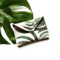 We love this envelope-style one of a kind, hand-painted leather wallet featuring a hand painted feathered palm print.