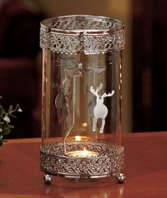 Bring seasonal cheer into your home with a Metal Spinning Snowflake Tea Light Holder. Just put your own tea light candle in the center cup, light it and the heat will cause the ornament to spin. Decorated silvertone borders on the glass enhance the o