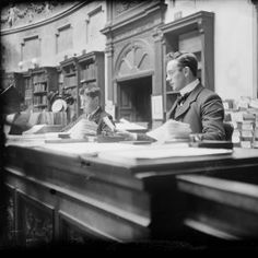 """""""Dubliners: The Photographs of JJ Clarke: A glimpse of James Joyce's Dublin 1897-1904,"""" via Google Cultural Institute -- Shown: """"The National Library of Ireland on Kildare Street was a bustling place full of young people, at the time...Joyce knew the librarians well, and set one of the chapters of 'Ulysses,' 'Scylla and Charybdis,' in the domed Reading Room... Library assistant and boy attendant in the Reading Room of the National Library."""" More at click-through."""