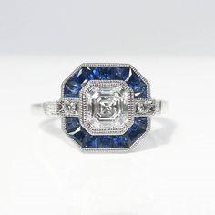 Asscher cut diamond with a sapphire halo. Designed by Kimberfire in Toronto. Asscher cut diamond with a sapphire halo. Designed by Kimberfire in Toronto. Asscher Cut Diamond Ring, Diamond Cuts, Diamond Rings, Art Deco Ring, Art Deco Jewelry, Jewelry Ideas, Deco Engagement Ring, Diamond Engagement Rings, Sapphire Bracelet
