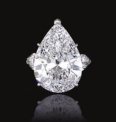 DIAMOND RING, HARRY WINSTON.  Claw-set at the centre with a pear-shaped diamond weighing 10.50 carats, flanked by similarly shaped diamonds, mounted in platinum,    signed Winston.