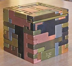 """5"""" sq all metal puzzle. Pieces must be slid in a special sequence, hidden keys and hidden storage space. Idea from Japanese puzzle boxes."""