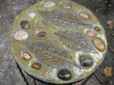 Cement poured into a pot  saucer and leaf imprinted with stones added, made for a friend. I made this for a friend... Bobbie Bradshaw    Color washed with acrylic paints and a clear over.