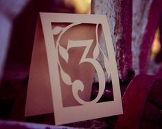 Papercut Table Numbers by MamaTita on Etsy. Put 2 LED tealight candles inside for a beautiful effect.