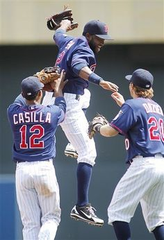 Minnesota Twins players Denard Span, center, Alexi Casilla and Brian Dozier celebrate after defeating the Oakland Athletics 4-0 in their baseball game Wednesday, May 30, 2012