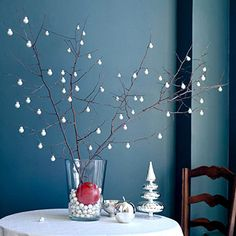 Hang mini white ornaments from tree branches to achieve the look of gently falling snow. More elegant holiday decorations: http://www.bhg.com/christmas/indoor-decorating/holiday-table-arrangements/?socsrc=bhgpin110712miniwhiteornaments#page=6