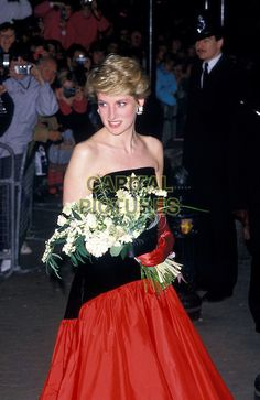 """HRH, THE PRINCESS DIANA OF WALES.Attending film premiere of """"The Mission"""", London, England,  October 1986..Lady Di royal half length strapless black and red top skirt dress mis-matched gloves holding bouquet bunch of flowers.Ref: CAP/PL.©Phil Loftus/Capital Pictures"""