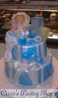precious moments baby shower cake blue with precioue moments baby on top with ribbons and rattles