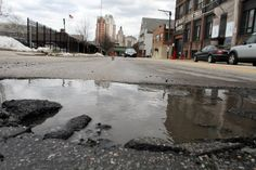 PROVIDENCE JOURNAL PHOTO / BOB BREIDENBACH,  A pothole filled with water looms large on West Exchange Street in Providence.