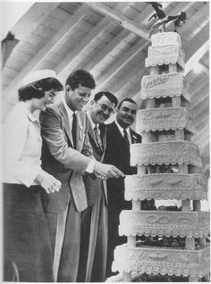Jackie, wearing a Chanel suit and a pillbox hat, laughs as JFK attempts to cut into a huge cake celebrating his forty-first birthday during a campaign stop in Fall River, Massachusetts.