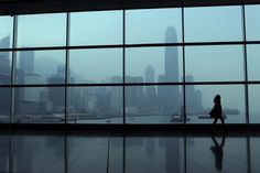 A woman walks past a tinted window in front of the city skyline in Hong Kong on December 27, 2012. With the global economic weakness continuing to impact domestic economy, the IMF said it expects Hong Kong's economy to grow 1.25 percent this year, before rebounding to three percent next year. (Dale de la Rey/AFP)