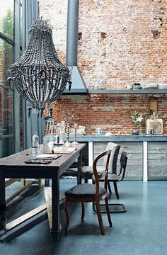 Rustic Eclectic kitchen with its mismatched dining furniture, over-sized chandelier and double-height brick wall, this kitchen-diner has a rough-luxe feel.