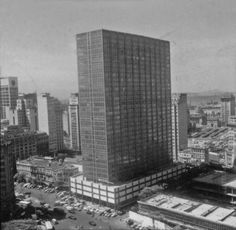 Estamos no início dos anos 60, pois o Ed. Av. Central já está concluído mas o da dese da Caixa ainda engatinha nos primeiros pavimentos, mas além de mostrar os dois prédios a foto, ajudada principalmente pela falta de verticalização na Rua da Ajuda nos mostra muito mais.