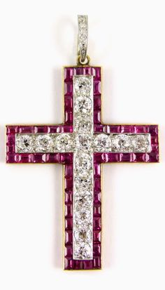 Antique ruby and diamond cross pendant, English c.1900, of Latin form, the straight sided arms set with a line of brilliant cut diamonds in a border of calibre cut rubies, on a detachable diamond line suspension hoop Length including hoop 6.7cms / 2 5/8'' Weight: 19g