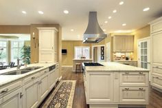 White painted flat ceiling with flush recess lights, stainless steel vent mounted in the middle of that ceiling, 2 white color painted islands with light color granite countertops, white color cabinets & doors then a nice dark hardwood floor.