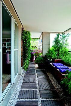 O destaque da varanda são os vasos com os mais diversos tipos de plantas. Mas os futons centralizam a atenção em meio ao verde, à madeira e os tons de terra