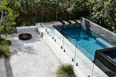 Designed by Acre - Munro Street. www.acre.com.au Photo by Derek Swalwell. Construction by Powda. View to pool with water spout features. Fire bowl and sunken seating area