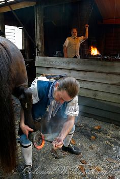 Farrier - Colonial Blacksmith fitting a red hot horse shoe to a horse at historic Colonial Williamsburg, Williamsburg, Virginia. - Photo by David M. Doody.