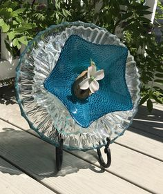 This Nature Land Candles offering is a clear etched glass platter with a blue glass bowl and ceramic Flower Yard Art. We get our pieces through estate sales and thrift stores. The base of this piece i
