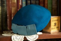 Lovely vibrant 1950s teal blue beret / cap  Features a firm brim and a lovely light blue / aqua square ribbon bow. It can be worn a number of ways. The hat is unlined. Fabric possibly Felt.  Makers mark: Hard to read) Merrmac Hat Corp Boxwood - Fiber   MEASUREMENTS Full Length: 9 Full width: 7 6/8 head circumference: 21 Height: Approx 4   CONDITION Very good condition. A few pucker marks when looking very closely. Not noticeable when worn. Just appears as some slight texture.