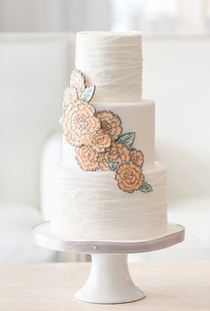 Jennfyer Mancino of The Sugar Suite created these modern, two-dimensional flowers by fashioning them from fondant and piping the petal details with pewter icing...  #weddings #weddingcakes #cakes.