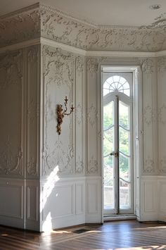 plasterwork walls, sconces, wood floors, wainscoting, French doors