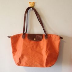 Large Orange Longchamp Le Pliage Tote Bag Pre owned bag with a lot of wear, particularly inside which has ink stains. Please see pics. Bag needs repair/cleaning -- please purchase with this in mind. Longchamp Bags Totes