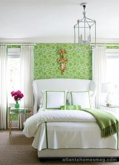 Margaret Bosbyshell Atlanta Homes Magazine white & apple green bedroom design with apple green floral wallpaper, white wingback bed with white & green bedding, brass mirrored nesting tables nightstands, apple green blanket, white curtains, sisal rug and white lamp.
