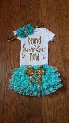 Adorable Gold glitter Bling brand sparkling new Onesie, lace ruffled bum bloomers, and Headband 3 piece set! **** long sleeved onesies available ****set can be made in other colors Onesie glitter in silver,gold, black, pink ..etc  Bloomers & headband in other colors as well..ex. pink,aqua,black, yellow  This 3 piece set includes:  - White Onesie adorned with gold glitter vinyl ( Carters brand onesie)  - Aqua lace ruffled bum bloomers adorned with a gold glitter detachable bow clip  - Aqua…