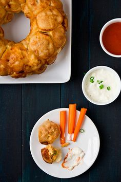 Buffalo chicken monkey bread  Ingredients  2 cloves garlic, thinly sliced  3 Tbsp butter  2 large chicken breasts, cooked and finely cut/shredded (~1 lb)  3/4 cup white onion, finely diced  1 Tbsp olive oil  1/3 cup wing sauce, plus more for serving  ~1.5 lbs pizza dough (I used 2 cans of Pillsbury pizza dough)  Bleu cheese or ranch dressing, for serving