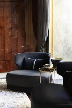 Black tub chairs sit snugly inside the gold leaf window arch. Design by Oliver Burns.
