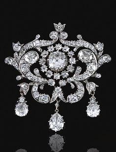 DIAMOND BROOCH, MID 19TH CENTURY. The central old-mine diamond in a cut-down collet within open work surrounds designed as foliate scrolls set with old-mine diamonds, suspending three pear-shaped diamond drops. #DiamondBrooches