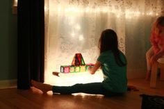 DIY light table with plastic storage box and Christmas lights.  Activities listed