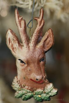 Dresden Christmas Ornament - Deer Head.  Rare single sided old Dresden Christmas ornament of a Deer Head, it is deeply embossed, two dimensional and shows fine details in its fur coat. Green oak leaves and gold acorns skirt the bottom. Loop hanger secured on backside.  ca. 1910-1920.  www.christmas.li