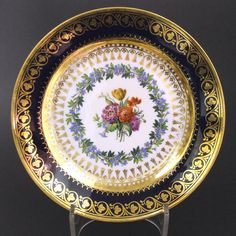 A Fine Sevres Porcelain Plate, Louis XVIII Period Dated 1821. The Center Decorated with Garden Flowers Surrounded by a Flowering Wreath. The Deep Blue Ground Border is Gilded in the Neo-Greek Style. The Base with a Painted Interlaced LLs Mark for Sevres. Further Painted Mark in Green for 1st May 1820, a Gilder`s Mark and an Incised Mark.