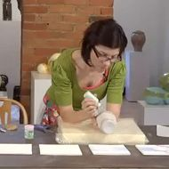 Photo of Erin Furimsky using slip trailing in her Ceramic Arts Daily Presents DVD Layered Surfaces.  Go to source for video clip.