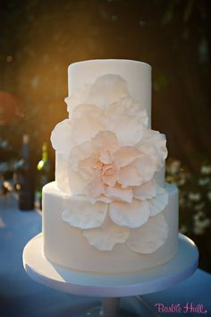 Cascading sugar rose petals in soft blushg pink on a three-tiered ivory wedding cake by Honey Crumb Cake Studio. Photo courtesy of Barbie Hull Photography (www.barbiehull.com).