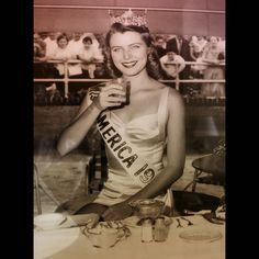 "Miss America 1958 - Marilyn Van Derbur -  ""This girl never got tired of smiling at me in my hotel room in Atlantic City this week.""  A small copper plate under the photograph reads: ""Having Breakfast On The Beach""."