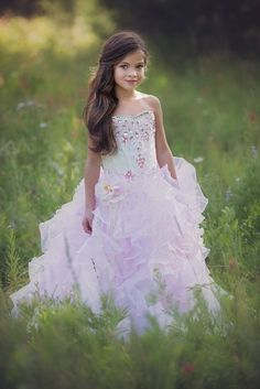 This couture ball gown in shades of blush and cream brings glamour and charm together in a design your little girl is sure to love! The dress is available in an array of stunning colors, ensuring you