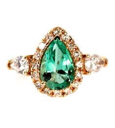 This lovely Emerald weighs over 2 carats and is surrounded by a halo of 1/2 carat in round brilliant diamonds. It is also flanked by 1 carat in pear shaped diamonds. The ring is crafted in 14k yellow
