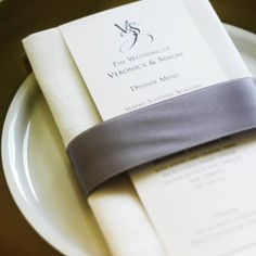 Wedding dinner menu napkins with teal ribbon and maybe a peacock feather