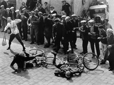 Two cyclists are involved in an accident at a sharp street corner in Fontainebleau during a Tour de France in the thirties.