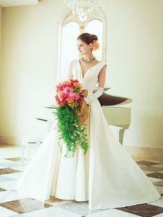 上質でエレガントなシルエットのドレスに、艶やかに映えるドラマティックなオレンジ色のブーケ