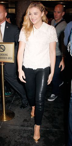 Chloe Grace Moretz toughened up a sweet white lace collared top with high-shine leather pants and metallic pumps.