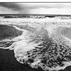 Eloi de La Monneraye - Langue de mer d'hiver, Jullouville - Nikon FM2 - Nikon 24mm f/2.8 AI-s - Ça reflète bien mon univers : bcp d'espace, de contrastes, les deux éléments terre mer sont réunis. Je pourrais montrer la même mer avec une eau turquoise. Là c'est en hiver, il y a un côté angoissant avec le grain qui tombe, le sable sombre.