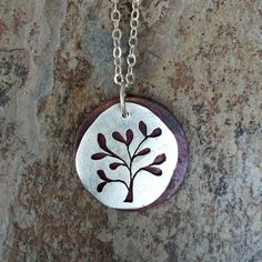 This necklace is made up of two discs. The first disc has been hammered down from a large ball of silver to give it a distinctive rustic look,