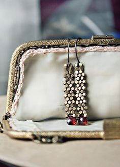 A cascade of brass ends in pretty garnet drops.