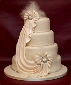 Cream colored cake with draping and feathers