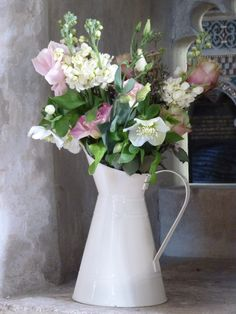 Vintage jugs of flowers including stocks, lisianthus, hellebores and vintage roses