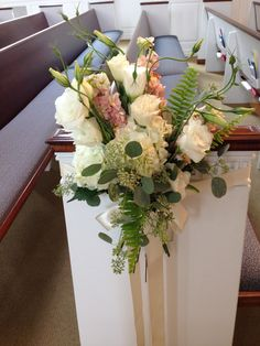 Pew marker made of white hydrangea, peach stock, white lisianthus, seeded eucalyptus, and fern.
